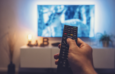 man Watching movie and using remote control