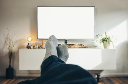 Człowiek ogląda telewizję w swoim salonie, punkt widzenia perspektywy. Zdjęcie Seryjne