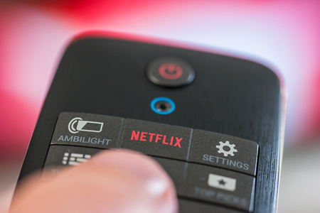 AACHEN, GERMANY OCTOBER, 2017: Man holds a remote control with a Netflix button. Netflix Inc. is an American company founded specializes in providing and providing online streaming media and video on demand.