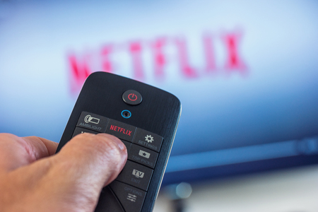 AACHEN, GERMANY OCTOBER, 2017: Man holds a remote control and selects a movie from Netflix. Netflix is ??an entertainment company, specializes in and provides streaming media and video on demand online.