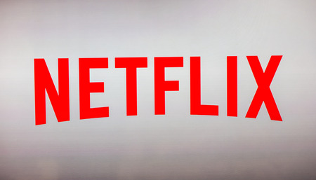 AACHEN, GERMANY OCTOBER, 2017: Netflix logo on a TV screen. Netflix app on laptop screen. Netflix is ??an international leading subscription service for watching TV episodes and movies. Editorial