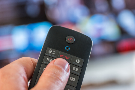 AACHEN, GERMANY OCTOBER, 2017: Man holds a remote control and pushes a netflix button. Netflix Inc. is an American company founded specializes in providing and providing online streaming media and video on demand. Editorial