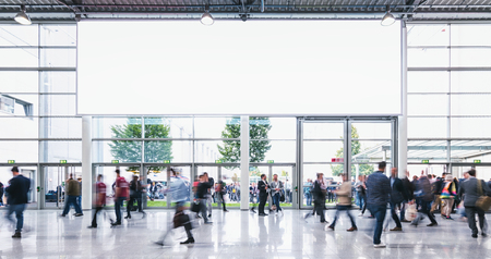 Anonymous Crowd of business people walking at a trade fair - concept image