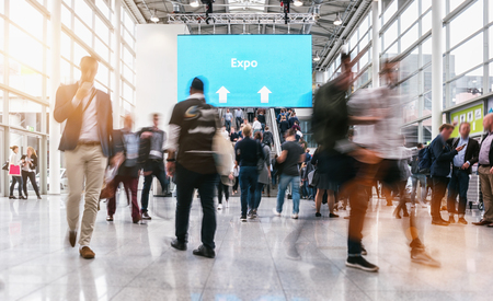 anonymous blurred people rushing at a expo