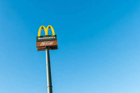 mcdonalds: COLOGNE, GERMANY OCTOBER, 2017: McDonalds restauraunt sign against blue sky. The McDonalds Corporation is the worlds largest chain of fast food restaurants.