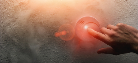 Hand Testing a home smoke alarm detector