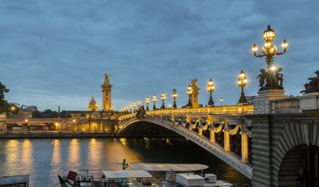 Pont Alexandre III Bridge Over River Seine and Hotel des Invalides at sunset. Bridge decorated with ornate Art Nouveau lamps and sculptures. Paris, France