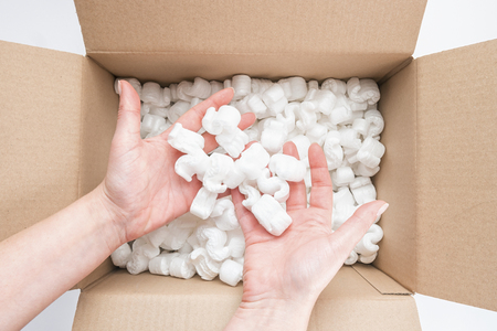 Closeup of female hands holding heap of packing peanuts in cardboard