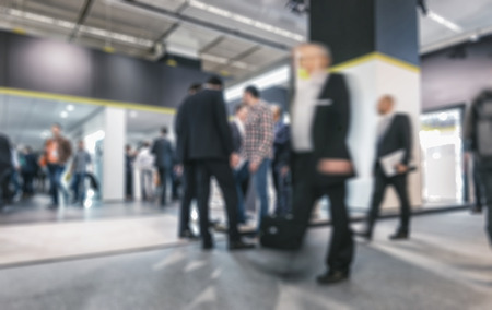 People walking on a trade show, generic background with a blue effect applied