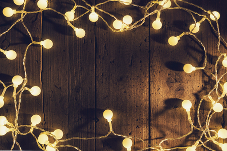 Christmas lights on wooden planks, with copyspace