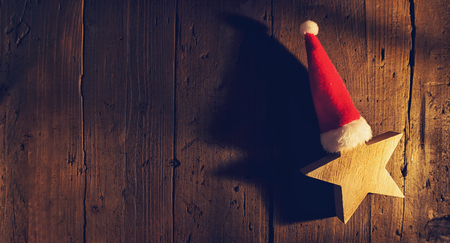 Christmas star with Santa hat on wooden background, elegant low-key shot, including copy space