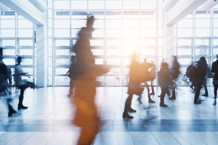 Folla di persone sfocate che camminano in un ambiente moderno