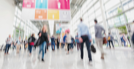 Intentionally blurred people walking trade show floor