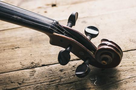 Antique violin head on a wooden floor Stock Photo