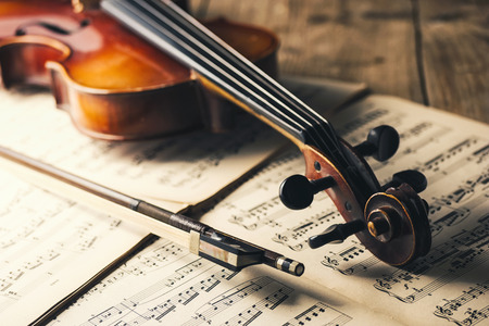 old violin with bow on notes