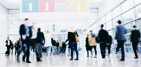 crowd of anonymous blurred business people at a trade fair Фото со стока