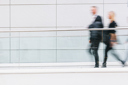 blurred business people walking in a futuristic corridor, including copy space