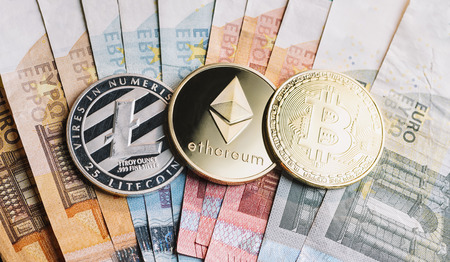 cryptocurrency coins - Litecoin, Bitcoin, Ethereum on top of Euro banknotes Фото со стока