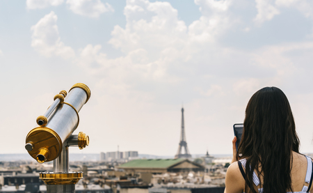 Telescope with view to the Eiffel tower and woman taking pictures with a smartphone in Paris