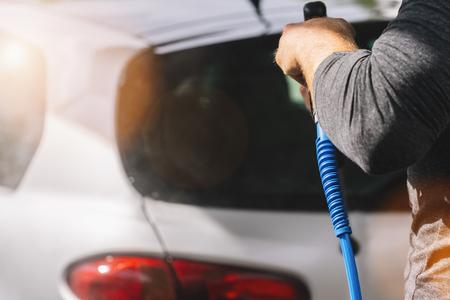 Man worker washing a car wash