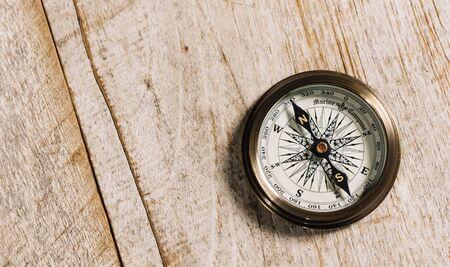 Stary kompas na koncepcji tła drewna dla kierunku, podróży, wskazówek lub pomocy