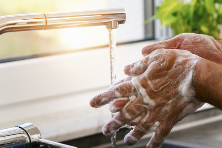 Man washing hands under water with soap