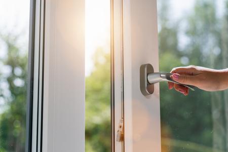 persona abre una ventana con luz solar Foto de archivo