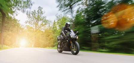 Motorbike riding on the forest road. Driving on the empty road on a motorcycle trip. copyspace for your individual text. 免版税图像 - 116871399
