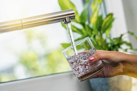 Frauenhand, die ein Glas hält, um es mit Wasser aus dem Wasserhahn anzuzapfen Standard-Bild