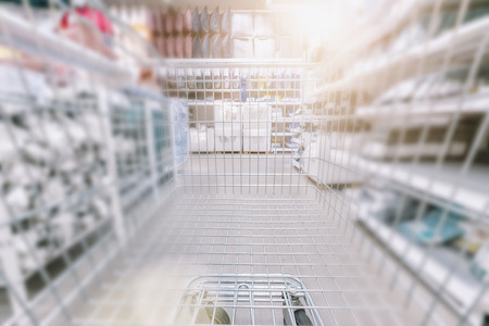 Shopping cart in supermarket aisle with product shelves abstract blur defocused background
