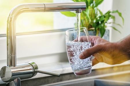 Hand met een glas water uit de keukenkraan Stockfoto