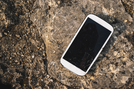 Broken screen smartphone on stone background