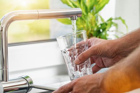 Nahaufnahme eines Mannes, der ein Glas frisches Wasser aus einem Küchenhahn gießt