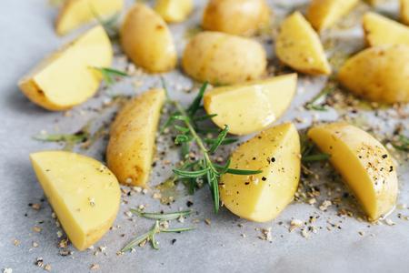 raw potato wedges on baking tray - homemade organic vegan vegetarian potato wedges snack food meal.
