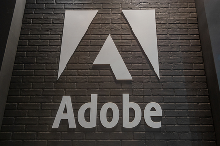 COLOGNE, GERMANY SEPTEMBER, 2018: Adobe Systems logo. Adobe is a multinational software company that produces and sells multimedia and creativity software. 報道画像