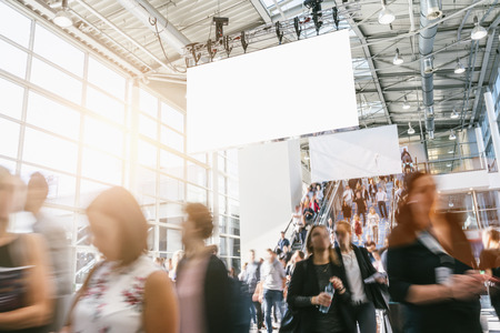 Crowd of blurred business people at a trade show, with copy space banner