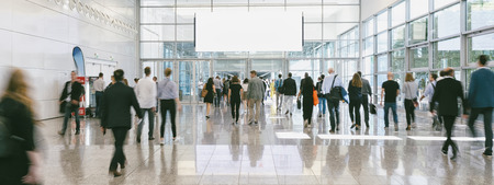 blurred business people at a trade fair, banner size, including copy space