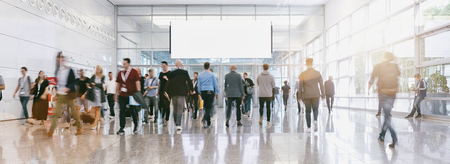 blurred business people at a trade fair, banner size