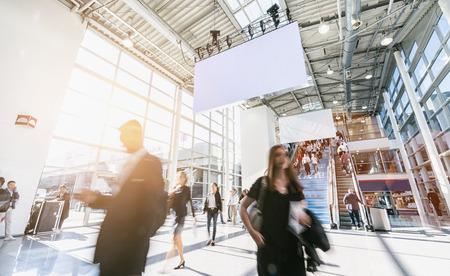 Gente de negocios borrosa en una feria comercial, incluido el espacio de copia Foto de archivo