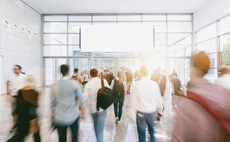 Crowd of anonymous people walking at a trade show, with copy space banner Stock Photo