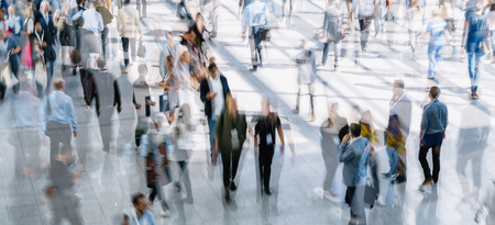 Crowd of anonymous people walking on busy city street Stock Photo