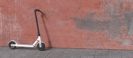 Electric scooter parked on a wall for mobility in the city Stockfoto