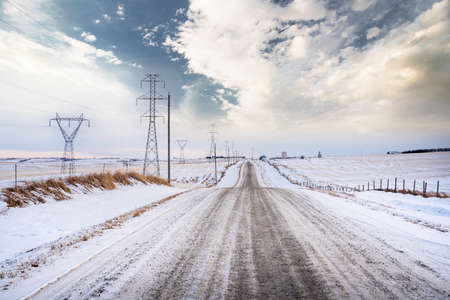 A rural gravel road along power lines and electrical transmission towers in Rocky View County Alberta Canada during the winter