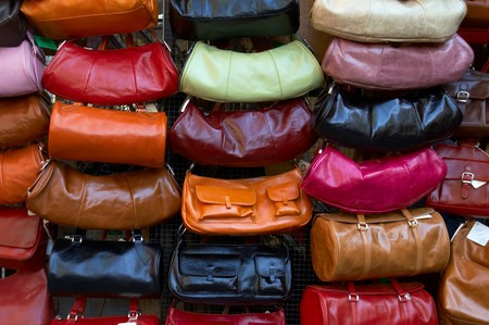 Display of leather purses of various colors, in an outdoor market in Florence, Italy.