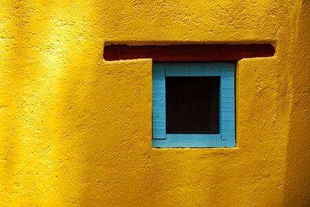 Rustic window in San Miguel de Allende, Spanish colonial town in Mexico. Blue turquoise window on a yellow wall.