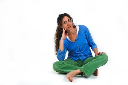 Attractive middle-aged caucasian woman with long brown hair, sitting cross-legged on floor.