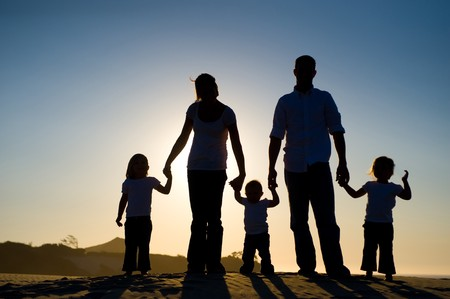 Beautiful silhouette of a family, with the sun setting behind them, standing on a hill. Stock Photo - 4039449