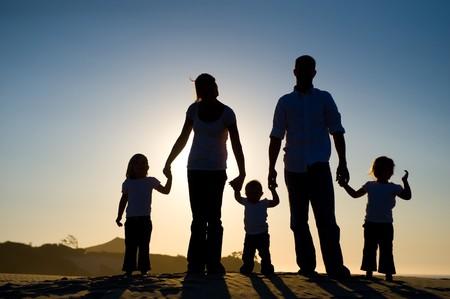 manos juntas: Bella silueta de una familia, con la puesta del sol detr�s de ellos, de pie sobre una colina. Foto de archivo