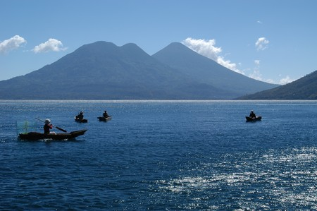 Men fishing in the traditional manner in Lake Atitlan, the largest lake of Guatemala photo