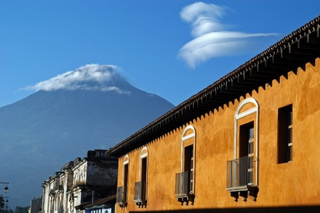 Cloud-capped volcano above old houses in Antigua, Guatemala.                                 Stock Photo